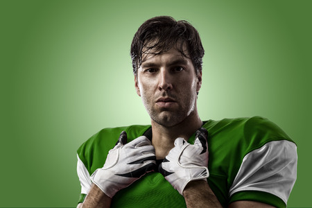 Football Player with a green uniform on a green background.