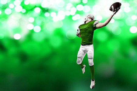 Football Player with a green uniform making a catch on a green lights background.