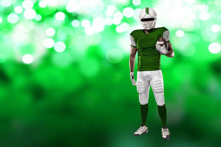 Football Player with a green uniform on a green lights background.