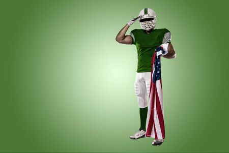 Football Player with a green uniform saluting with a american flag, on a green background. Stock Photo