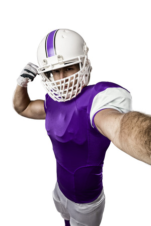 Football Player with a purple uniform making a selfie on a white background.