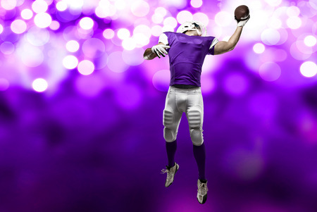 Football Player with a purple uniform making a catch on a purple lights background. Stock Photo