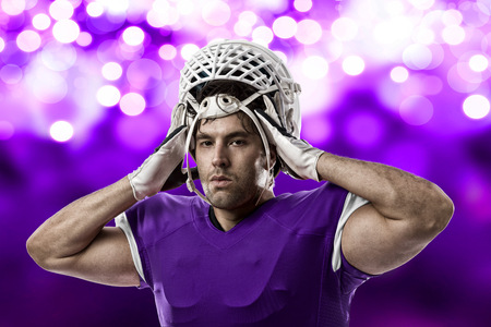Football Player with a purple uniform on a purple lights background. Stock Photo
