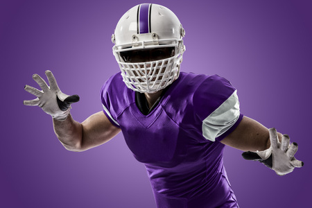 Football Player with a purple uniform making a tackle on a purple background. Stock Photo