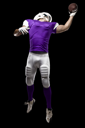 Football Player with a purple uniform making a catching on a black background. Stock Photo