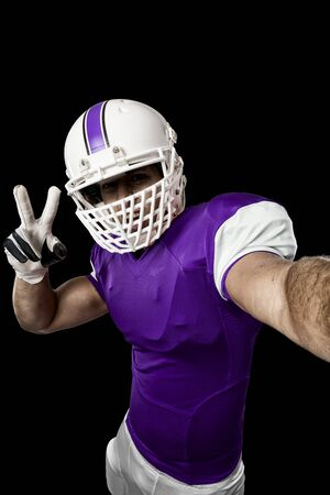 Football Player with a purple uniform making a selfie on a black background.