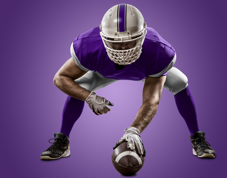 Football Player with a purple uniform on the scrimmage line, on a purple background.