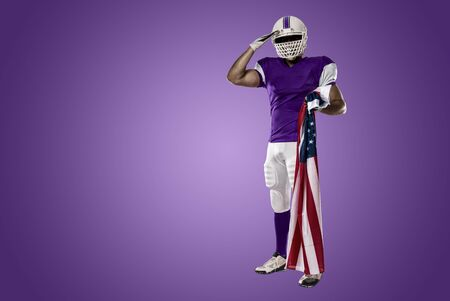 Football Player with a purple uniform saluting with a american flag, on a purple background. Stock Photo