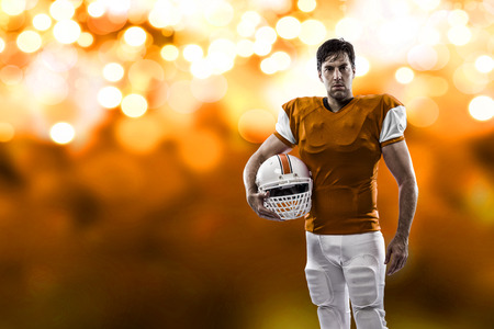 Football Player with a orange uniform on a orange lights background.