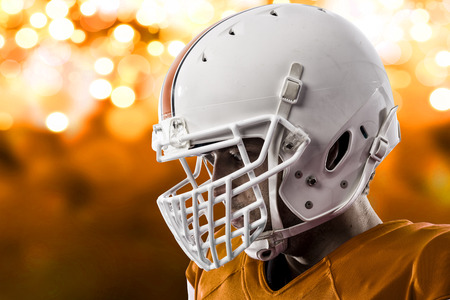 Close up of a Football Player with a orange uniform on a orange lights background.