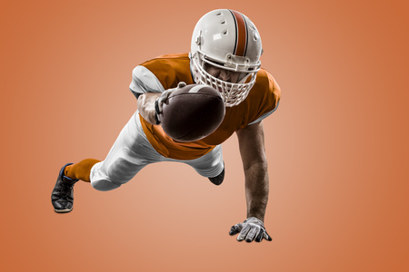 Football Player with a orange uniform scoring on a orange background. Stock Photo