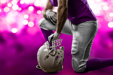 Football Player with a pink uniform on his knees, on a pink lights background. Stock Photo