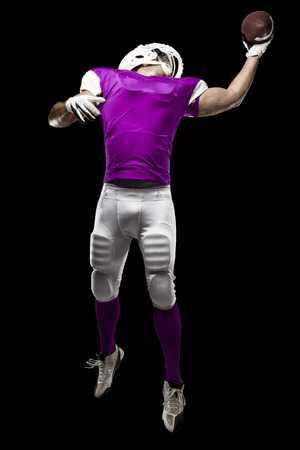 Football Player with a pink uniform making a catching on a black background.