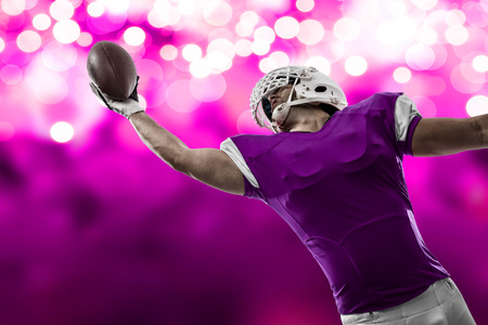 Football Player with a pink uniform making a catch on a pink lights background.