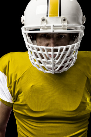 Close up of a Football Player with a yellow uniform on a black background.