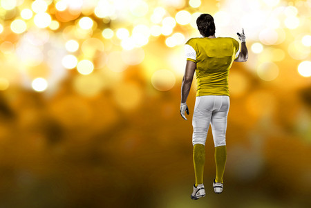 Football Player with a yellow uniform walking, showing his back on a yellow lights background.