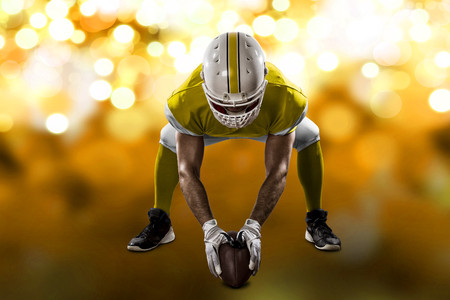 Football Player with a yellow uniform on the scrimmage line, on a yellow lights background.
