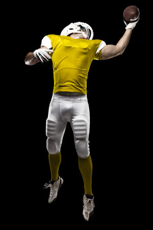 Football Player with a yellow uniform making a catching on a black background.