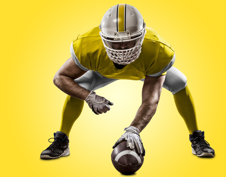 Football Player with a yellow uniform on the scrimmage line, on a yellow background. Stock Photo