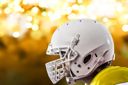 Close up of a Football Player with a yellow uniform on a yellow lights background. Stock Photo