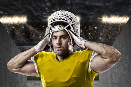 Football Player with a yellow uniform on a stadium tunnel. Stock Photo