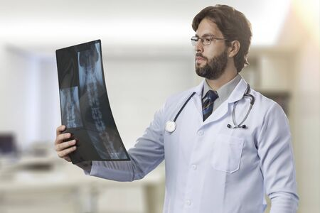 Male doctor in his office looking at a x-Ray.