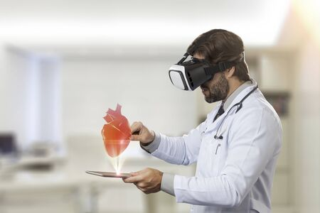 virtual office: Male doctor in his office,using a Virtual Reality Glasses, looking at a virtual heart. Stock Photo