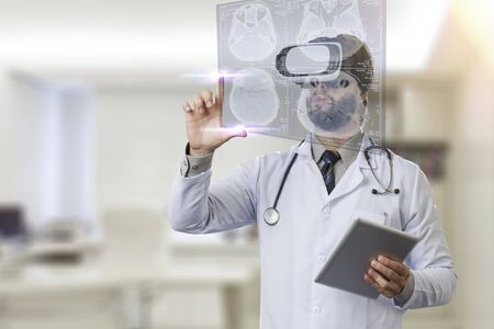 virtual office: Male doctor in his office, using a Virtual Reality Glasses, looking at a virtual screen.