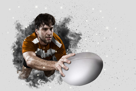 Rugby Player with a orange uniform coming out of a blast of smoke .