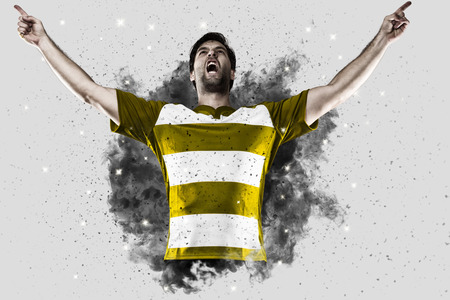 Rugby Player with a Yellow uniform coming out of a blast of smoke . Stock Photo