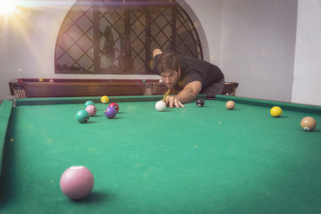 snooker hall: Man playing billiards in a pool table.