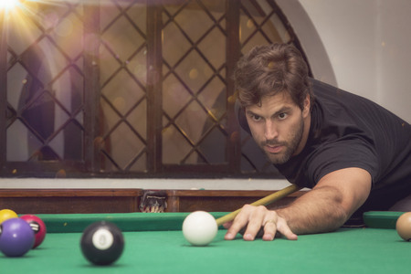 Man playing billiards in a pool table. photo