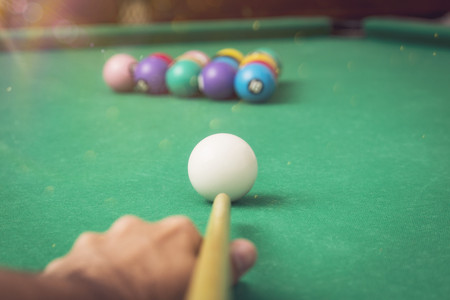 snooker halls: Man playing billiards in a pool table.