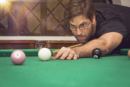 billiards halls: Man playing billiards in a pool table.