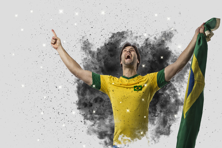 Brazilian soccer player coming out of a blast of smoke. celebrating. Stock Photo