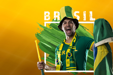 Brazilian male fan, celebrating on a yellow background with copy space.