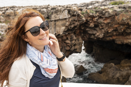 Woman posing in front of Devils Throat, Garganta do diabo, rock formation in Cascais, Portugal