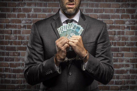Brazilian man holding bills of money with a handcuff in a jail. concept of corruption, corrupt politicians, illegal businesses. brick background.