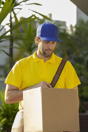 Brazilian mailman delivering a package on the street. Internet purchase being delivered at home.