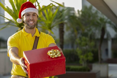 Brazilian mailman dressed as Santa Claus delivering a gift. Online purchase being delivered. Zdjęcie Seryjne