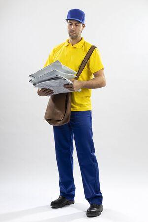 Brazilian mailman on a white background delivering a package. copy space. Zdjęcie Seryjne