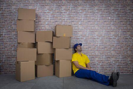 Brazilian mailman sleeping in a deposit with a a lot of boxes. Zdjęcie Seryjne