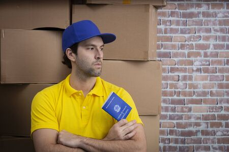 Brazilian mailman holding work book, Brazilian social security document, in a deposit with a a lot of boxes.
