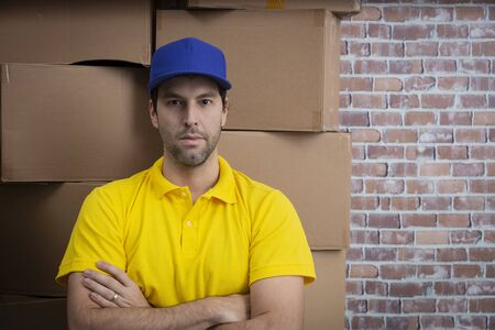 Brazilian mailman with arms crossed in a deposit with a a lot of boxes.