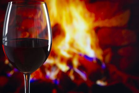 Glass of Wine on a wooden table in front of a fireplace