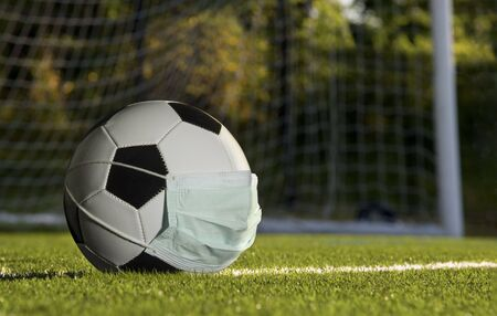 soccer ball wearing a mask, concept of sports suffering from the COVID-19 pandemic.
