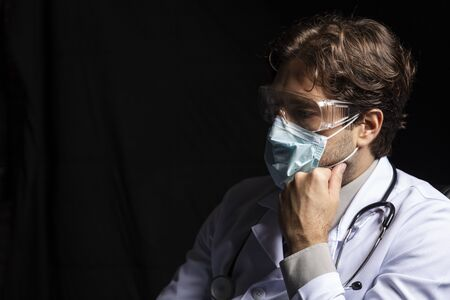 male doctor wearing a mask and goggles, tired of working with covid-19 on a black background.