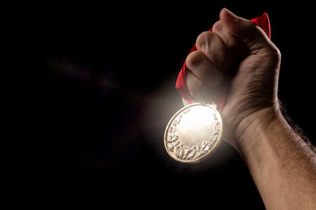 hand holding a gold medal on black with blank face for text, concept for winning or success Standard-Bild