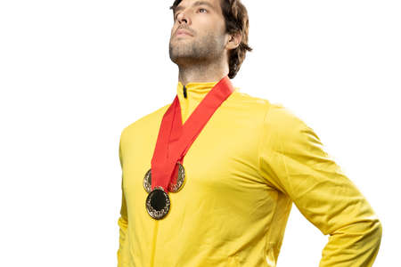 male athlete smiling after winning a gold medal in a white background. Sportsman with medal celebrating his victory.