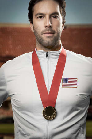 American male athlete smiling after winning a gold medal in a stadium. Sportsman with medal celebrating his victory. Standard-Bild